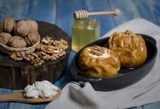 Alimento sano Mele al forno con la ricotta e bugia matta in un piatto bollente nero su una tavola di legno blu fotografie stock