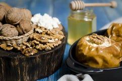 Alimento sano Mele al forno con la ricotta e bugia matta in un piatto bollente nero su una tavola di legno blu immagini stock