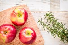 Alimento sano: mele e rosmarini rossi sulla tavola di legno Fotografia Stock
