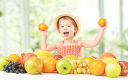 Alimento sano muchacha feliz del niño y una fruta Foto de archivo libre de regalías