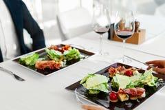 Alimento sano Pares que comen el restaurante de Caesar Salad For Meal In Imagenes de archivo