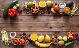 Alimento sano, selezione pulita dell'alimento: frutti, verdure, semi, spezie sui bordi marroni con il posto per testo Immagine Stock Libera da Diritti