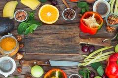 Alimento sano, selezione pulita dell'alimento: frutti, verdure, semi, spezie sui bordi marroni con spazio libero per un testo Immagini Stock Libere da Diritti