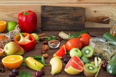 Alimento sano, selezione pulita dell'alimento: frutti, verdure, semi, spezie sui bordi marroni con spazio libero per un testo Immagini Stock
