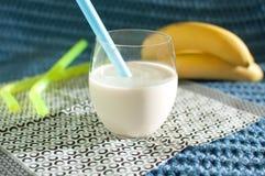 Alimento sano Smoothies del plátano Batido de leche y plátanos maduros en fondo azul de la tela Fotografía de archivo libre de regalías
