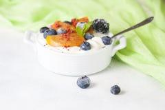 Alimento sano, spuntini o yogurt greco casalingo della prima colazione con i mirtilli, le more, i cachi e la menta Su una pietra  Fotografia Stock Libera da Diritti