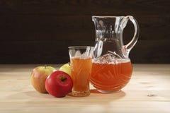 Alimento sano Un jarro con el zumo de manzana recientemente exprimido cerca de manzanas maduras y un cristal en una tabla de made Fotos de archivo