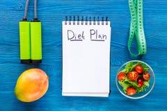 Alimento saporito per dimagrire Taccuino per il piano di dieta, l'insalata, i frutti ed il nastro di misurazione su derisione blu Immagini Stock Libere da Diritti