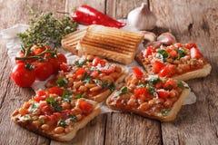 Alimento saudável: brinde com feijões brancos, tomates, queijo e garli Imagem de Stock