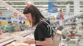 Alimento saudável de compra da jovem mulher no supermercado venda, compra, consumi??o e conceito dos povos video estoque