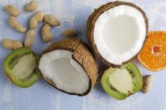Alimento saudável fresco do veg Coco, amendoins, fruto de quivi, alaranjado no fundo azul fotos de stock