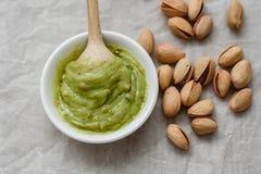 Alimento saudável, massa do pistache e pistaches salgados unpeeled, colher de madeira em um fundo claro Componentes para cozinhar fotos de stock