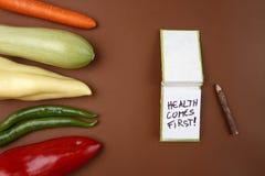 Alimento saudável: Os vegetais crus na saúde marrom do ` do fundo e da mensagem vêm primeiramente! ` Fotografia de Stock