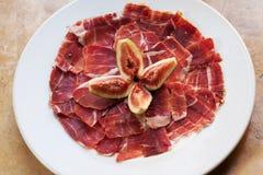 Alimento spagnolo Jamon dei tapas di cucina con il fico Belle fette di appetito di carne suina cruda, fondo bianco del piatto Immagine Stock Libera da Diritti