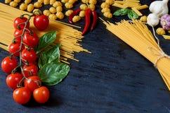 Alimento, spezie ed ingredienti tradizionali italiani per cucinare: il basilico va, pomodori ciliegia, aglio, peperoncino, pasta immagini stock