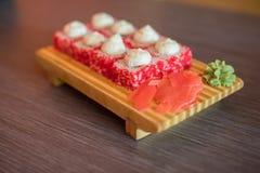 Alimento su un piatto di legno dei rotoli di sushi con il pesce e ric giapponesi Fotografia Stock Libera da Diritti
