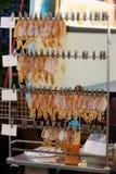 Alimento tailandês da rua, calamares secados, grampeado em ordem e pendurada no fio de metal fotos de stock
