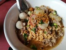 Alimento tailandês da rua: macarronete imediato com bolas de peixes, porks vermelhos na sopa picante fotos de stock