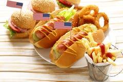 Alimento tradicional do cachorro quente, das batatas fritas e dos anéis de cebola para a celebração do 4 de julho Fotografia de Stock Royalty Free
