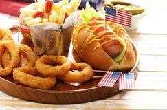 Alimento tradicional do cachorro quente, das batatas fritas e dos anéis de cebola para a celebração do 4 de julho Fotos de Stock