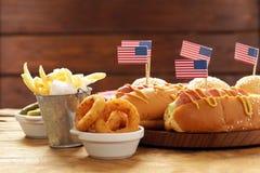 Alimento tradizionale del hot dog, delle patate fritte e degli anelli di cipolla per la celebrazione del 4 luglio Immagine Stock