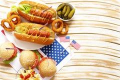 Alimento tradizionale del hot dog, delle patate fritte e degli anelli di cipolla per la celebrazione del 4 luglio Immagini Stock