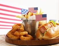 Alimento tradizionale del hot dog, delle patate fritte e degli anelli di cipolla per la celebrazione del 4 luglio Immagini Stock Libere da Diritti