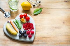 Alimento vegetariano di stile di vita sano nel cuore e stetoscopio con il concetto del fondo della medicina alternativa dell'acqu fotografia stock libera da diritti