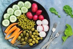 Alimento vegetariano Le verdure su un piatto, ravanello, cetriolo, carote, hanno inscatolato i piselli, capperi marinati, foglie  Fotografie Stock Libere da Diritti