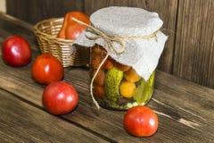Alimento Verduras conservadas hechas en casa en tarros Tomates adobados y foto de archivo libre de regalías