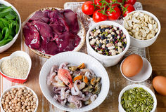 Alimentos altos no ferro, incluindo ovos, porcas, espinafres, feijões, seafoo Imagem de Stock