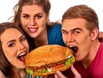 Alimentos de preparación rápida de la hamburguesa en manos de los amigos de la gente Imagen de archivo