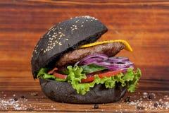 Alimentos de preparación rápida, hamburguesa negra apetitosa, presentada maravillosamente en un fondo de madera imágenes de archivo libres de regalías