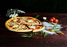 Alimentos de preparación rápida italianos Pizza caliente deliciosa cortada y servida en el disco de madera con los ingredientes,  foto de archivo