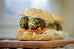 Alimentos de preparación rápida vegetarianos - hamburguesa del falafel en el tablero de madera Imagenes de archivo