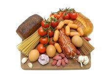 Alimentos diferentes em uma placa de corte em um fundo branco Fotos de Stock Royalty Free