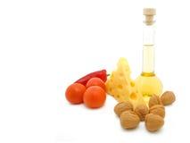 Alimentos naturais do formulário. Queijo, petróleo, porca e tomate. Fotos de Stock
