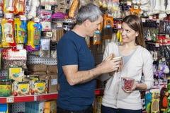 Alimentos para animais de estimação de compra dos pares na loja Foto de Stock