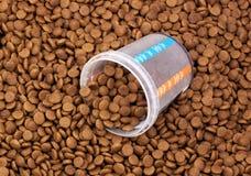 Alimentos para animais de estimação marrons secos com medida do vidro Foto de Stock Royalty Free