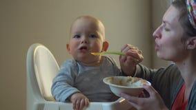 Alimentos para niños La mamá alimenta al bebé con una cuchara del puré de la fruta El bebé rechaza comer y los gritos metrajes