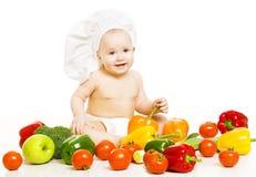Alimentos para niños Niño en el sombrero del cocinero que se sienta dentro de verdura sobre blanco Imagen de archivo libre de regalías