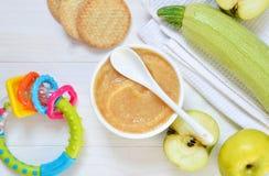 Alimentos para niños a partir de 6 meses Puré vegetal de los calabacines, de los sellos y de las patatas en un fondo concreto C imagenes de archivo