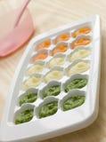 Alimentos para niños hechos puré en una bandeja del cubo de hielo Fotos de archivo libres de regalías