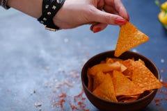 Aliments de préparation rapide d'ordure mangeant des chips de prise de main de frites de nacho photos libres de droits