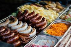 Aliments de préparation rapide de rue dehors, saucisses frites, fond Photographie stock