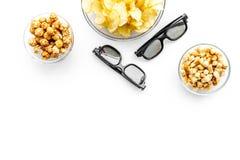 Aliments de préparation rapide pour le film de observation Chips, maïs éclaté, biscottes près des verres sur le copyspace blanc d Photo stock
