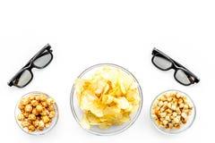 Aliments de préparation rapide pour le film de observation Chips, maïs éclaté, biscottes près des verres sur le copyspace blanc d Photos stock
