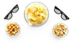 Aliments de préparation rapide pour le film de observation Chips, maïs éclaté, biscottes près des verres sur le copyspace blanc d Photos libres de droits