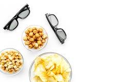 Aliments de préparation rapide pour le film de observation Chips, maïs éclaté, biscottes près des verres sur le copyspace blanc d Images libres de droits