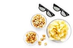 Aliments de préparation rapide pour le film de observation Chips, maïs éclaté, biscottes près des verres sur le copyspace blanc d Photographie stock libre de droits
